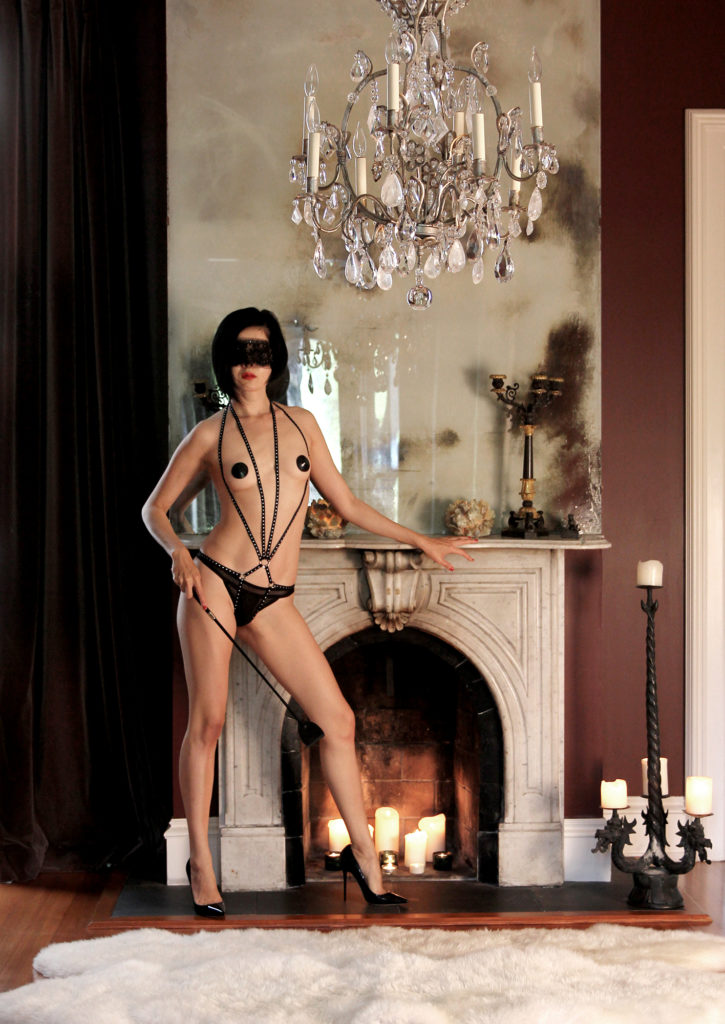 Femdom Domina Yuki stands in leather lingerie in front of a fireplace holding a riding crop. Good slaves are rewarded with body worship.
