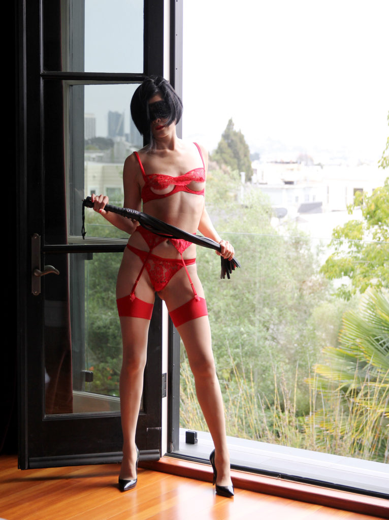 San Francisco Asian Dominatrix in lacy red lingerie, stiletto heels, next to a window holding a leather flogger.