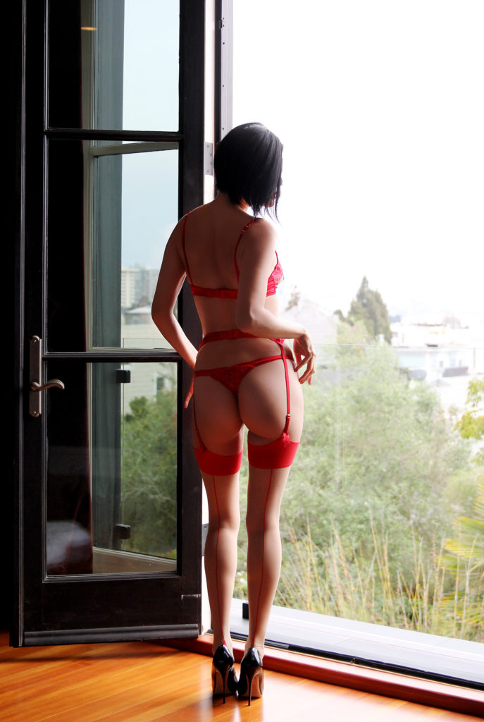 San Francisco based Dominatrix wearing lacy red lingerie and thong with her back turned to the camera.