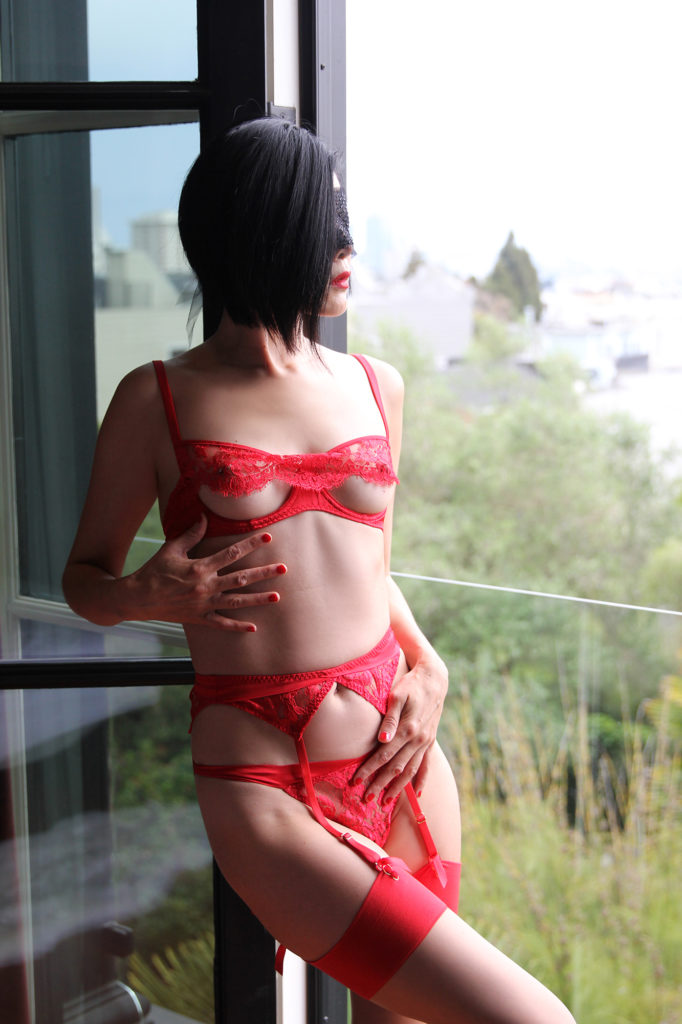 Asian Femdom Domina Yuki wearing lacy red lingirie looking at the distance off of a balcony.