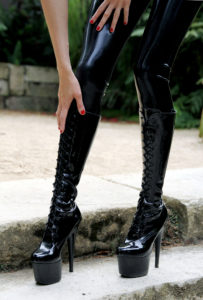 Asian Pro domme running a hand over her patent leather knew high boots. Domina Yuki loves leather and latex.