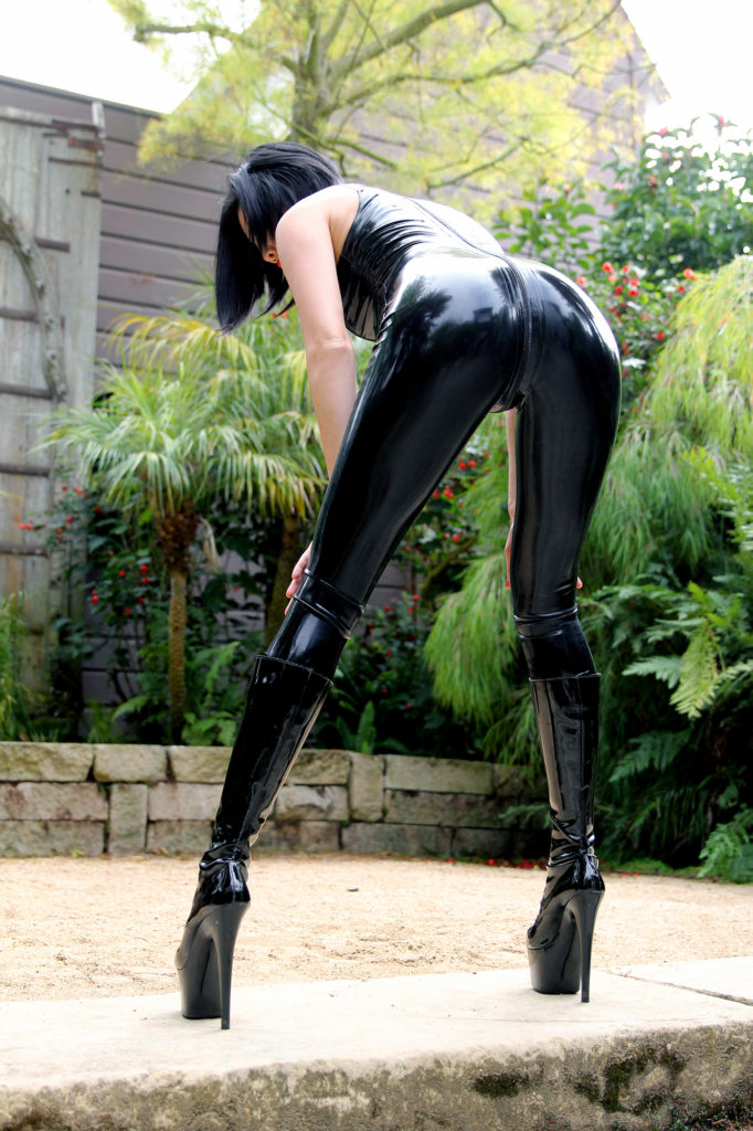 Asian Dominatrix in a San Francisco garden bending over in leather wearing knew high stiletto heeled boots.