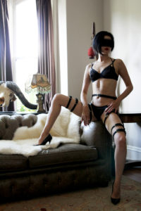 San Francisco Asian Dominatrix sitting on a couch wearing black lingerie, leather straps, and stiletto heels with her legs spread