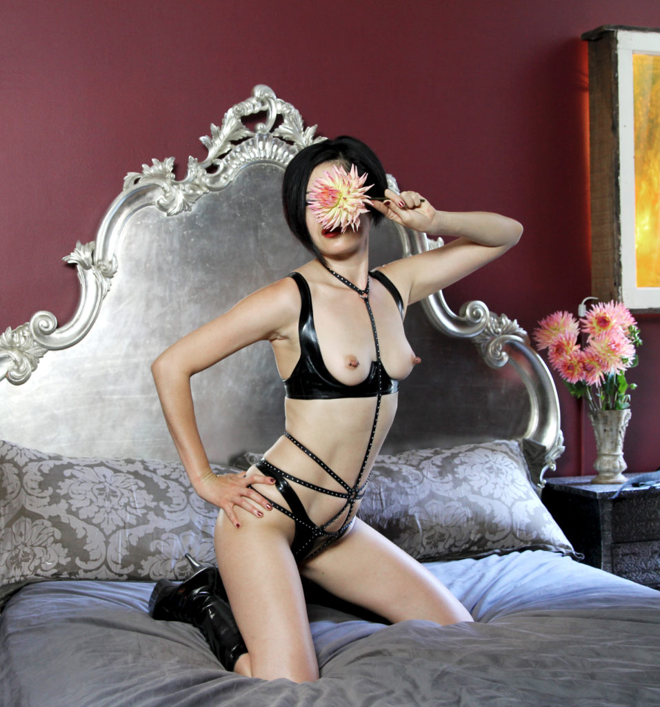 Dominatrix Domina Yuki kneels on a bed while wearing leather lingerie. She specializes in bespoke BDSM fantasy experiences.