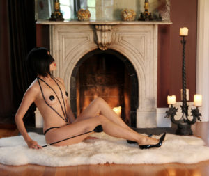Domina Yuki reclined in front of a San Francisco fireplace wearing elegant leather lingerie and holding a riding crop.