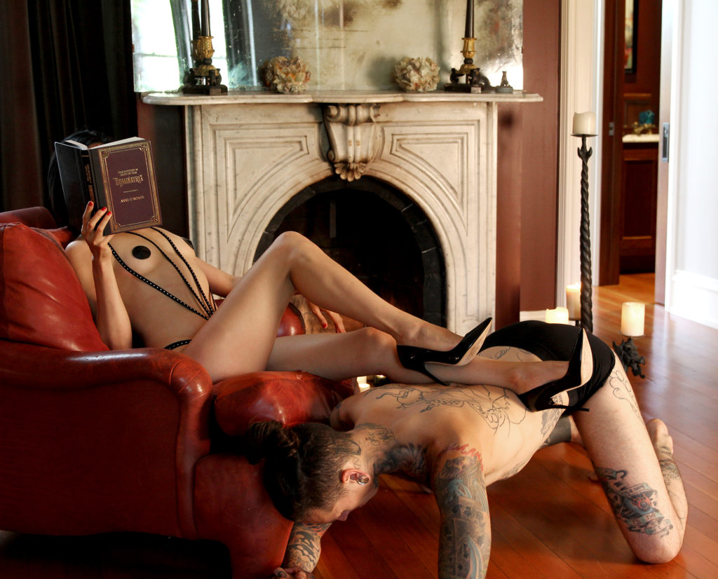 San Francisco Dominatrix Domina Yuki reclines in a leather chair while resting her stiletto heels on her male slave.