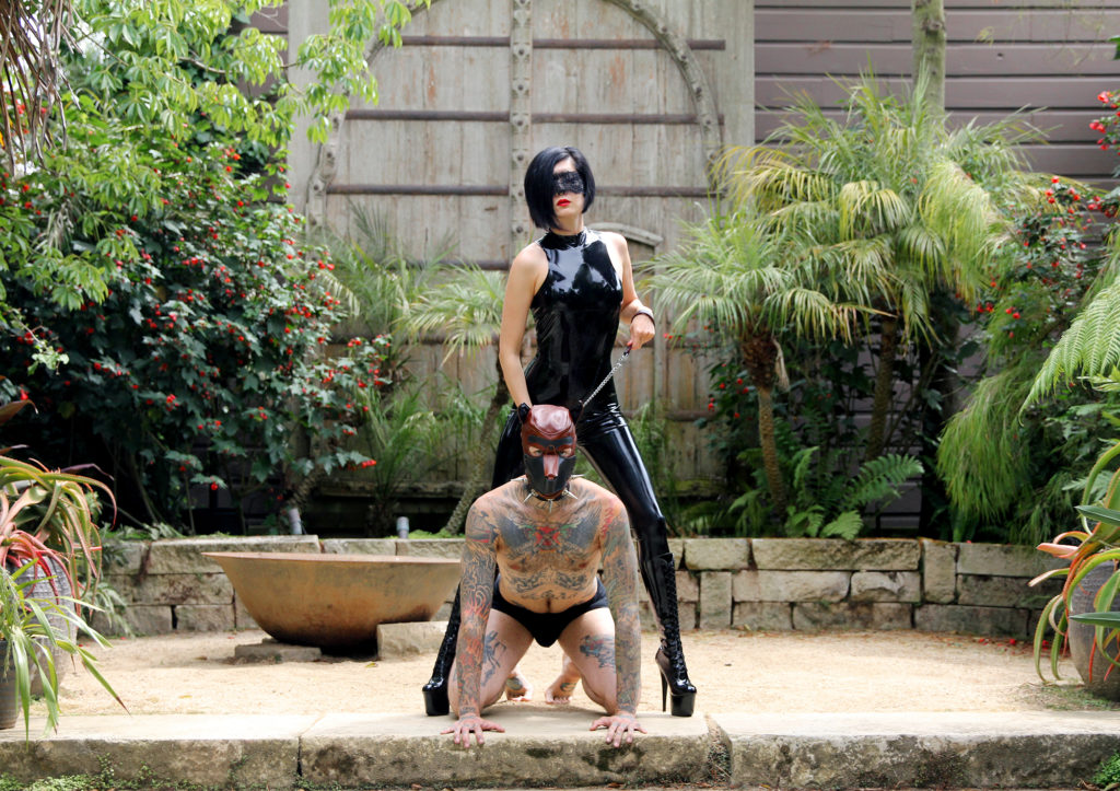 Professional Asian Dominatrix stands in a garden with her male slave on a dog leash. She enjoys total power exchange and bondage.