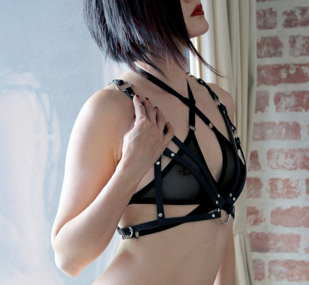 Oakland and San Francisco Asian Dominatrix Domina Yuki in black lingerie and a leather bondage harness.