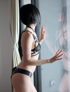 San Francisco Dominatrix Domina Yuki wearing black lingerie and a leather bondage harness reflected in the glass of a window.