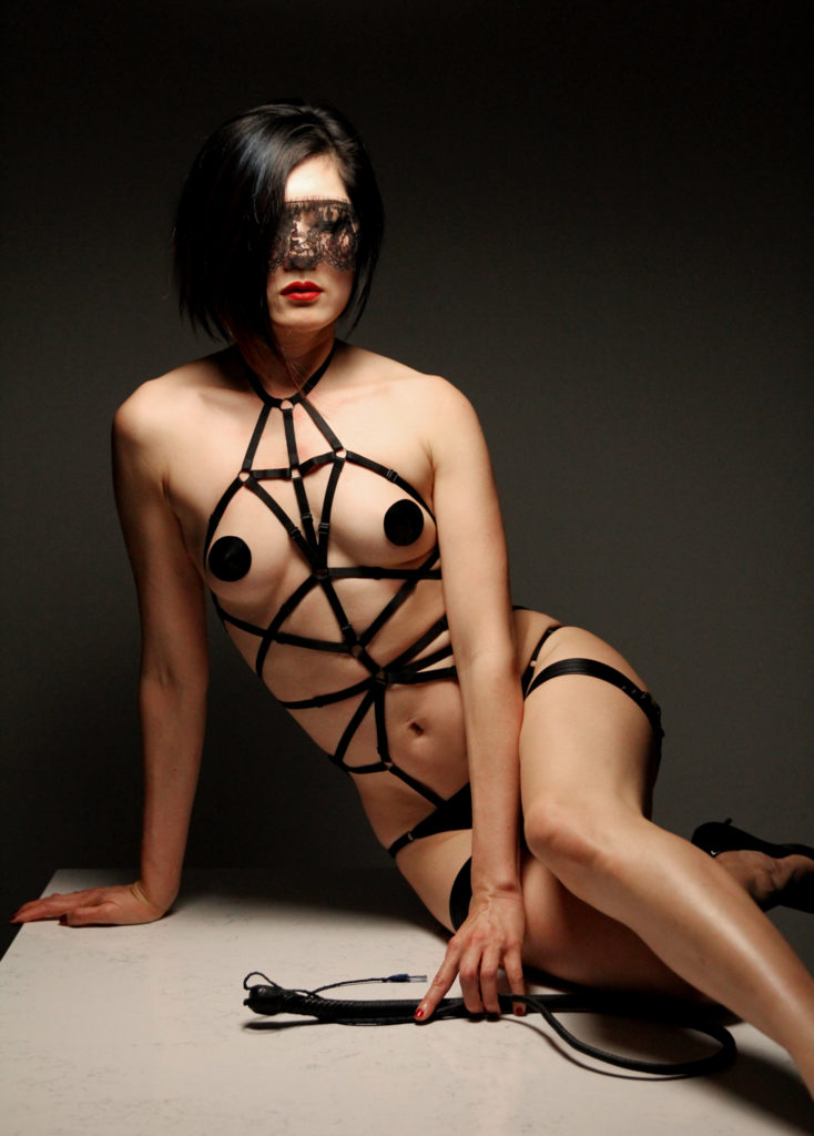 Dominatrix Domina Yuki sitting propped on one arm wearing a leather bondage harness her hand placed on a whip.