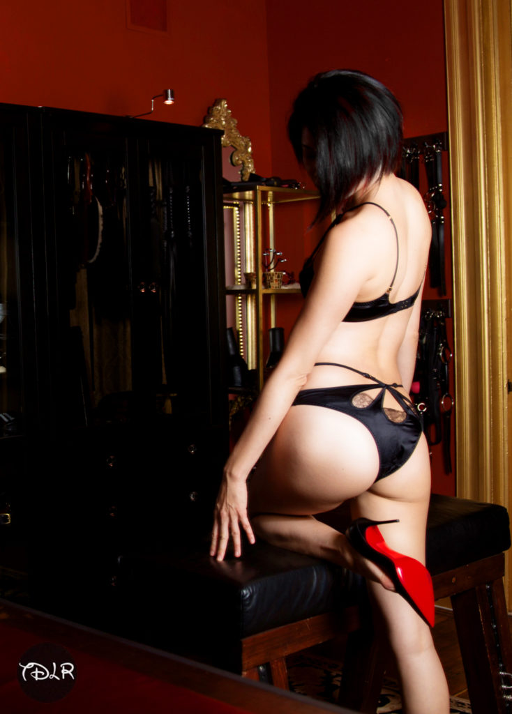 Asian Pro domme Domina Yuki with her back facing the camera, wearing dark lingirie and red soled stiletto heels.