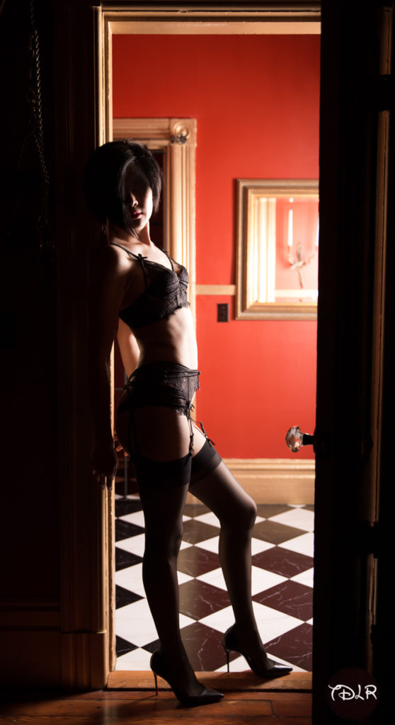 Oakland and San Francisco based Dominatrix Domina Yuki standing in a doorway wearing delicate dark purple lace lingerie.