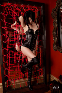 Asian Femdom Domina Yuki in delightful leather attire with leather thigh high boots grabbing a red web.