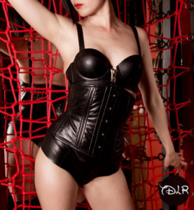 Oakland and San Francisco based Asian Dominatrix wearing leather and a leather corset, grasping a red web.