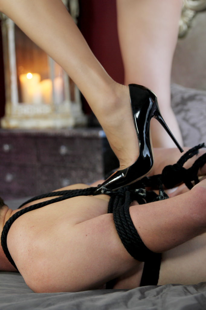 San Francisco Dominatrix in stilettos standing on the back of her rope bound male submissive.