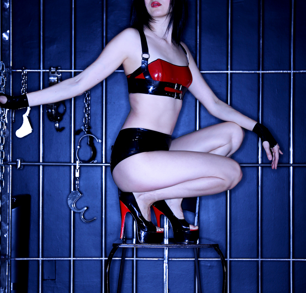 Crouching in red heeled high heels, San Francisco Asian Dominatrix Domina Yuki looks to the distance next to handcuffs.