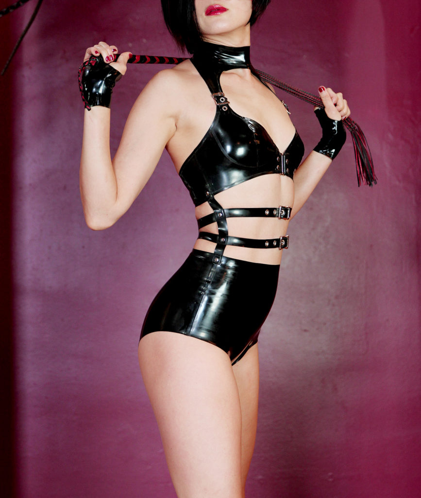 Asian Dominatrix Domina Yuki requires worship as she stands in elegant leather lingerie holding a flogger.