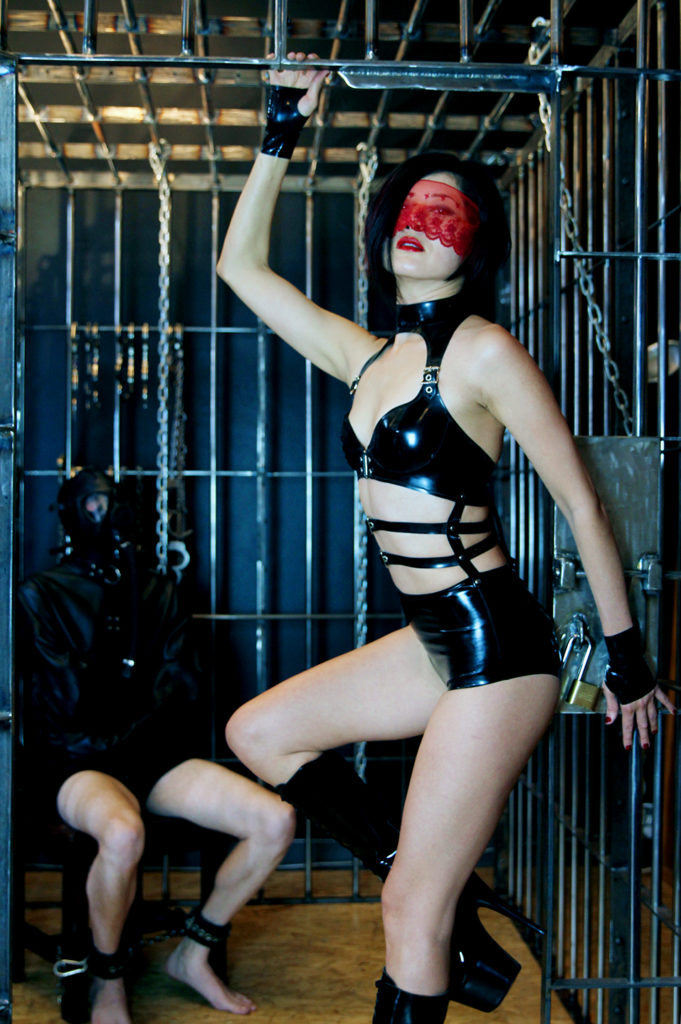 Pro domme Domina Yuki stands in a San Francisco dungeon next to her male submissive bound to a chair in a cage