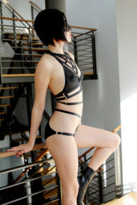 San Francisco Dominatrix Domina Yuki standing in black lingerie and boots next to a stairway.