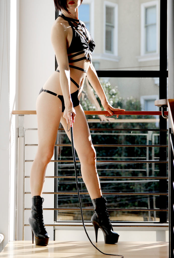 Asian Dominatrix Domina Yuki standing in black lingerie with a whip used in both her San Francisco and Oakland play spaces.