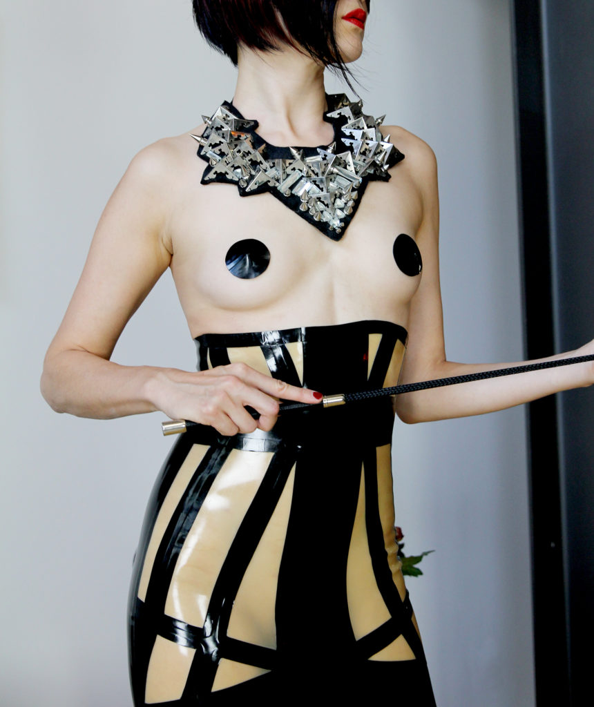 San Francisco Asian Dominatrix standing in a latex dress with an ornate neckless holding a riding crop.