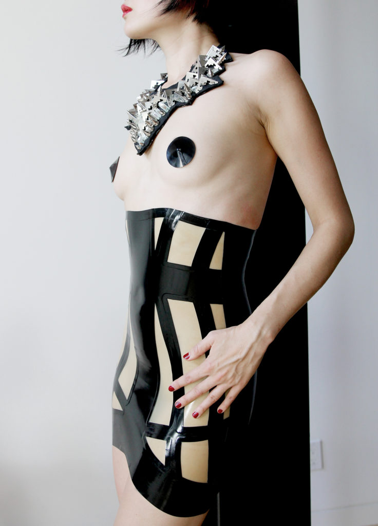 Asian Femdom based in Oakland and San Francisco standing in a latex dress with an ornate silver neckless.