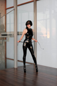 Asian Dominatrix Domina Yuki wearing a latex body suit holding a whip. She enjoys bondage, CFNM, and fetish.
