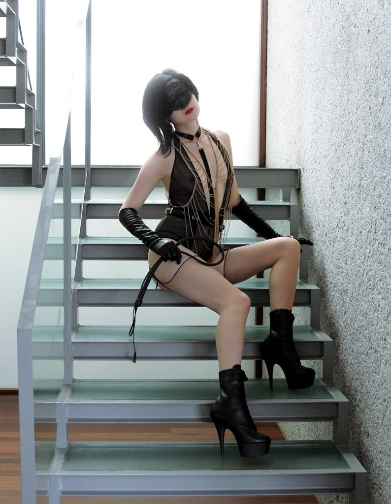 Oakland Asian Femdom Yuki sits holding a whip wearing lingerie, leather gloves, and stiletto boots.