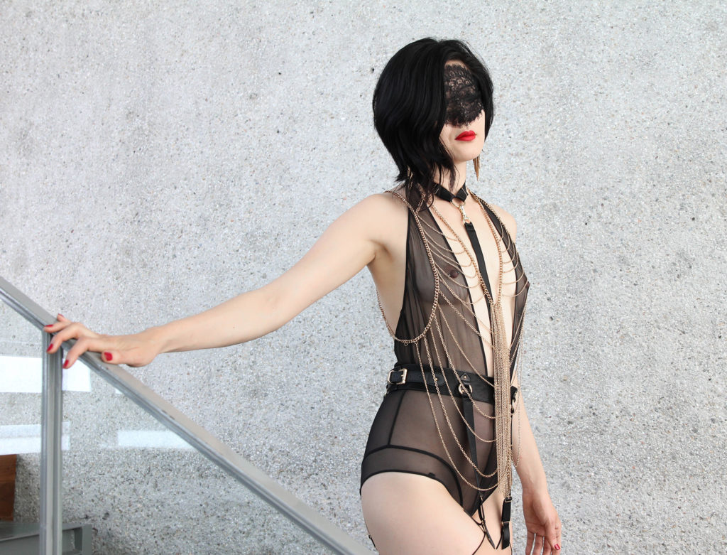 Standing in elegant chains and black lingerie, San Francisco Dominatrix Domina Yuki tempts all male submissives to serve.