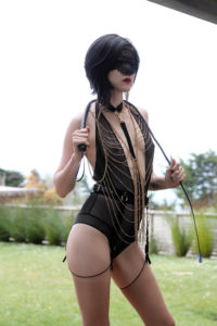 Standing in a garden wearing black lingerie and holding a whip, Asian Dominatrix Domina Yuki beckons you to serve her.