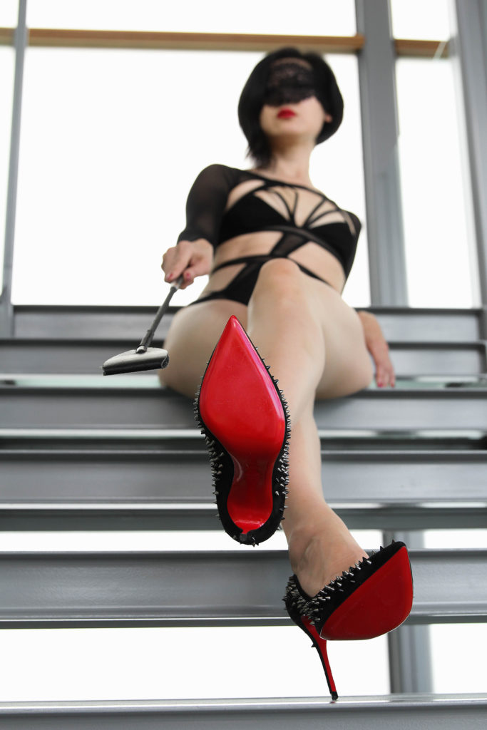 Asian Dominatrix Domina Yuki wearing lingerie and spiked heels, demanding male submissive to serve and worship.