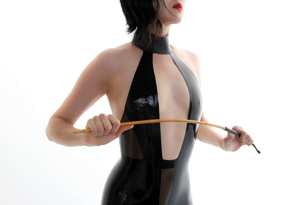 Oakland Asian Dominatrix Domina Yuki in a leather dress holding a riding crop. She enjoys bondage, CFNM, and fetish.