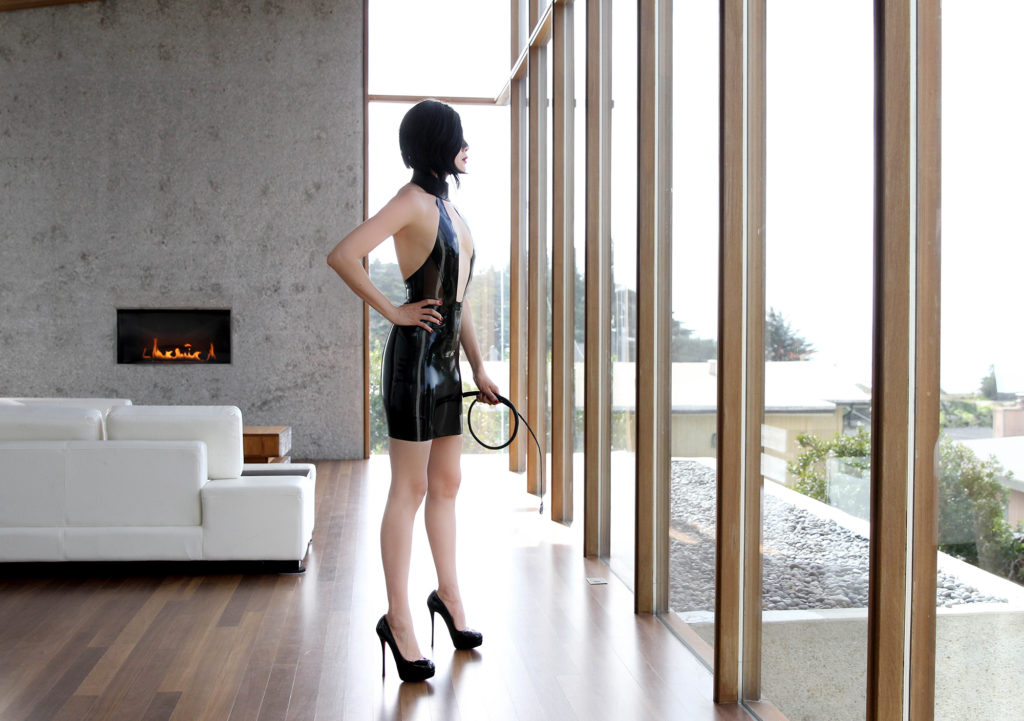 Asian Femdom Domina Yuki stands in a leather dress and stilettos, holding a whip. She beckons male submissive to serve.