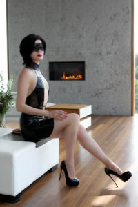 San Francisco Asian Dominatrix Domina Yuki in front of a fireplace wearing an elegant leather dress and stilettos.