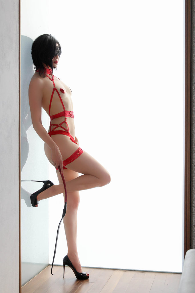 San Francisco Asian Pro domme Domina Yuki in red lingerie and stilettos. She enjoys CFNM, bondage and total power exchange.