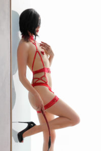 Oakland and San Francisco Asian Dominatrix Domina Yuki in red lingerie and stilettos holding a flogger.
