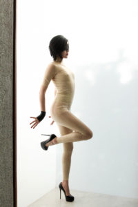 San Francisco Femdom, Domina Yuki, posing next to opaque glass wearing an enticing latex body suit and stiletto heels.