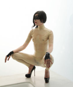 Domina Yuki, an Oakland and San Francisco based Dominatrix, squatting in a translucent latex body suit and stiletto heels.