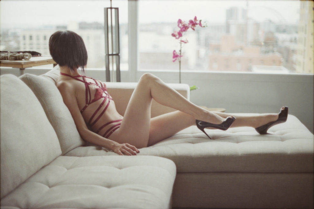 San Francisco Dominatrix, Domina Yuki, reclining on a white couch wearing red lingerie and stiletto heels.