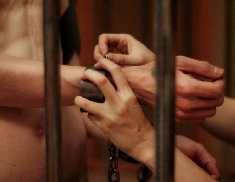 Pro domme Domina Yuki affixing shackles to her caged male submissive.