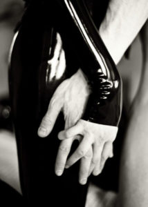 Asian Dominatrix Domina Yuki's latex sleeved arm entwined with a male submissive's.