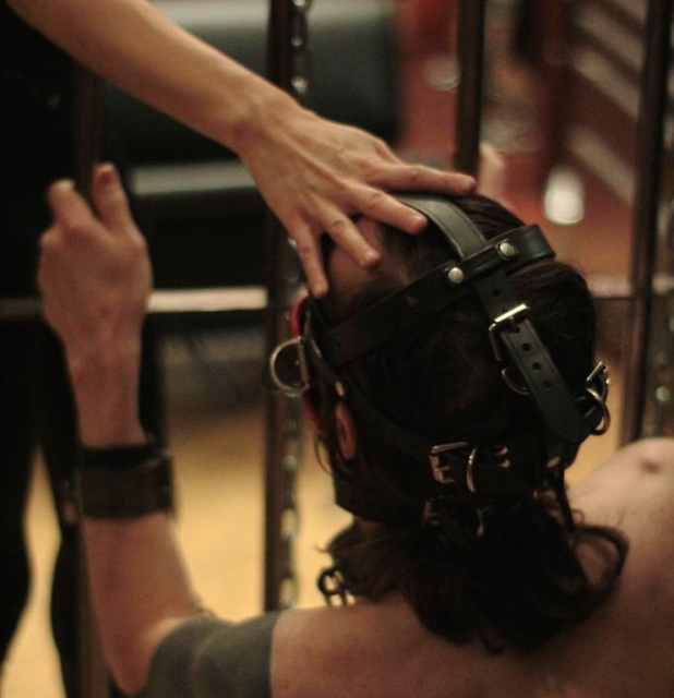 Professional Dominatrix Domina Yuki demands obedience from her male slave bound in a leather mask and leather cuffs.