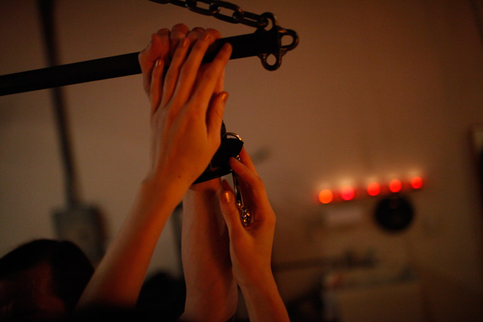 Asian Dominatrix Doimina Yuki's hands affix hand cuffs, preparing for an evening of bespoke fetish and fantasy experience.