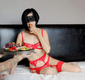 Elegant Professional Dominatrix Domina Yuki lounges in red lingerie while her male slave serves her a fig.