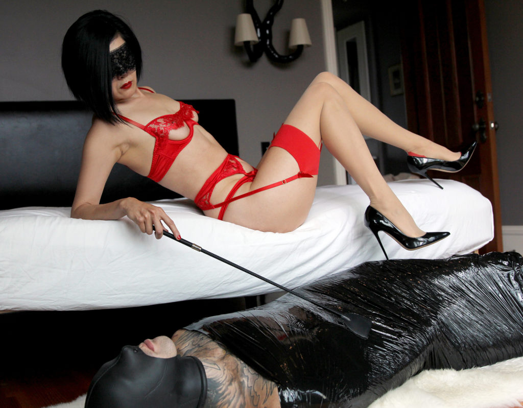 Asian Prodomme Domina Yuki reclines in red lingerie while teasing her bound and masked submissive with a riding crop.