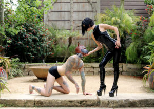 A devoted submissive slave in a leather dog mask obeys Asian femdom Domina Yuki's every command.