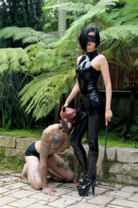 Wearing latex and stiletto boots, Prodomme Domina Yuki pets her submissive who heels at her side on his hands and knees.