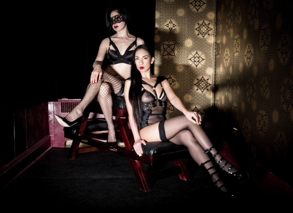 San Francisco Dominatrix Domina Yuki sits with a friend in lingerie. Yuki provides premier fetish and kink experiences.