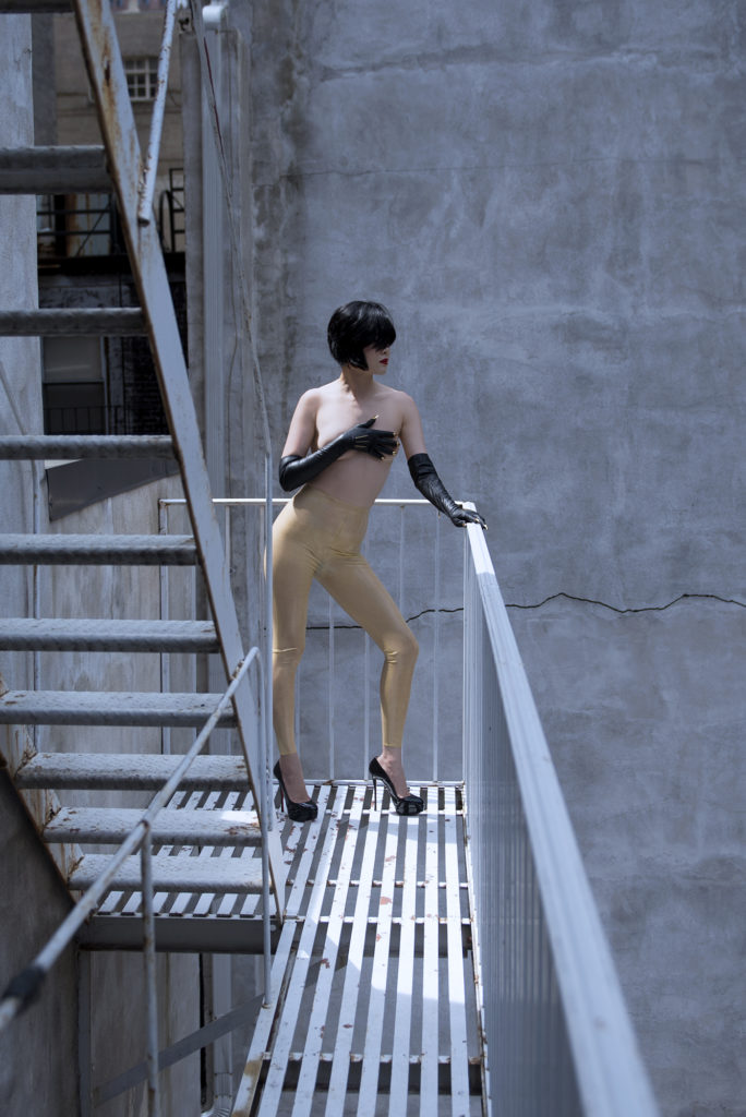 Professional Dominatrix Domina Yuki stands on a fire escape elegantly dressed and covering her breasts with gloved hands.
