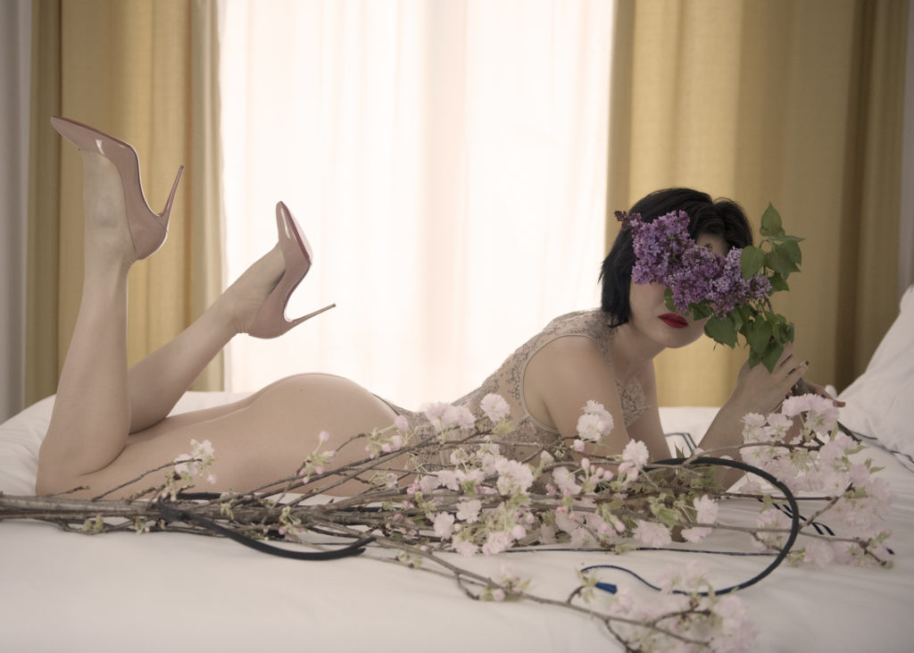 Asian Femdom Domina Yuki masks her face with flowers while laying on a bed. She excels in helping you explore your kinks.
